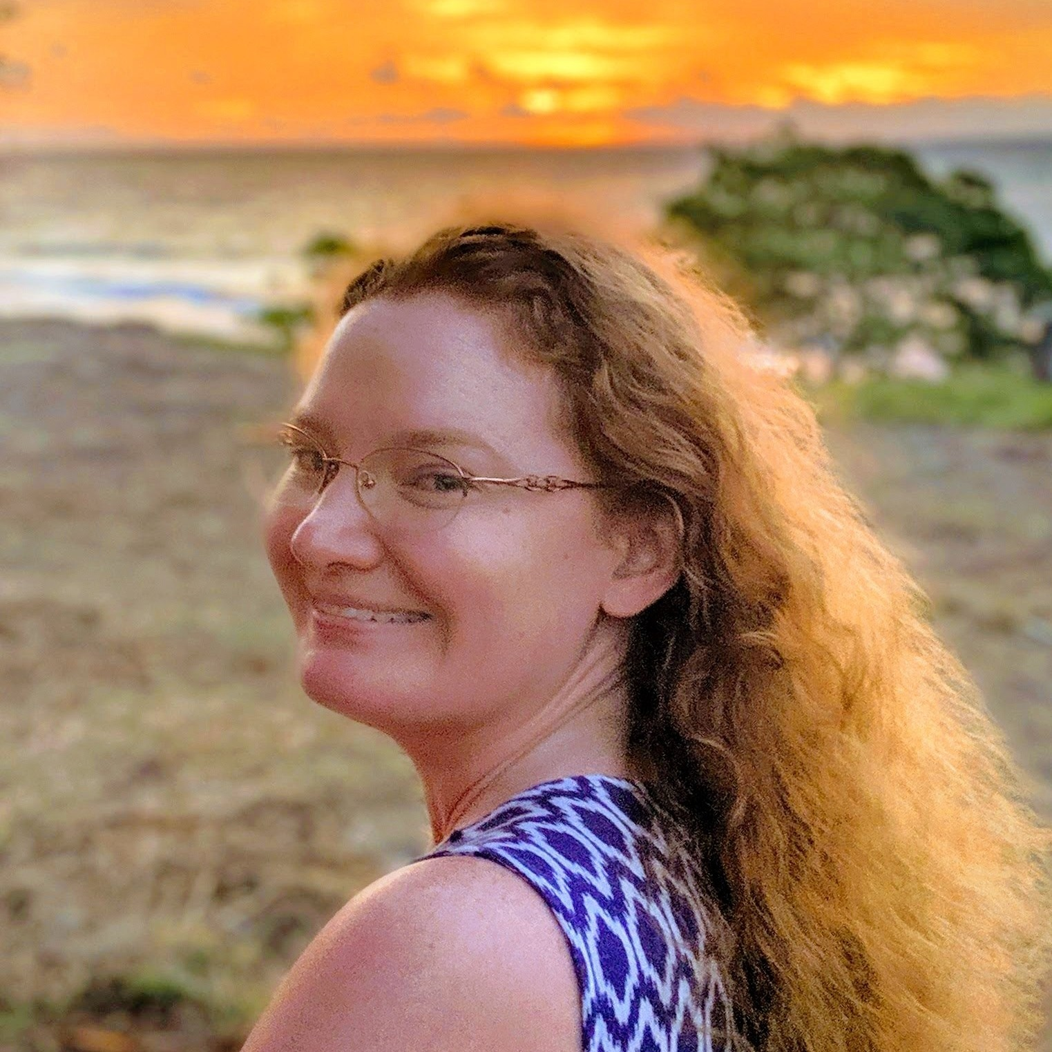 Photo of a red haired woman with glasses on a beach with sunrise in the background